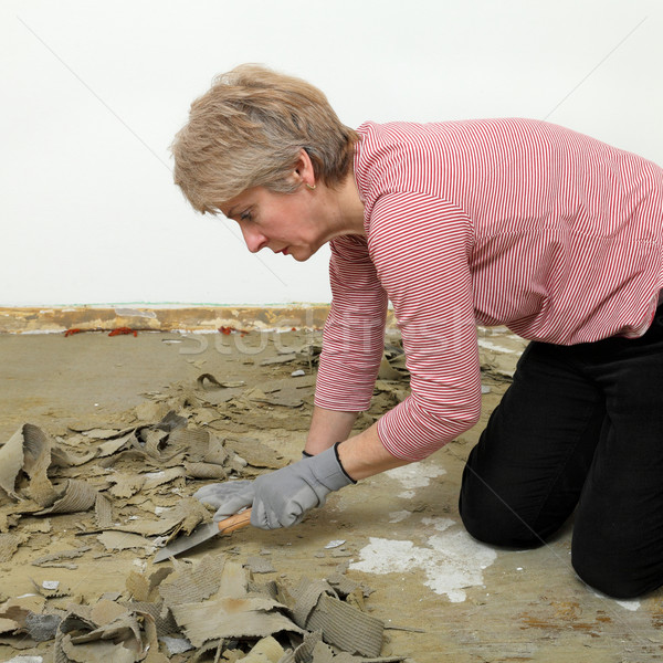 Female worker using putty knife for cleaning floor Stock photo © simazoran