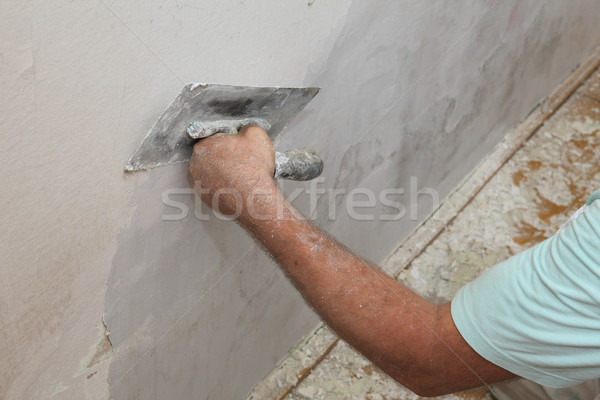 Worker spreading plaster to damaged wall Stock photo © simazoran