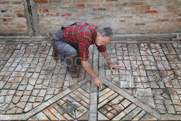 Pavement or terrace making, worker placing piece of tile Stock photo © simazoran