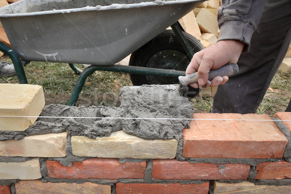 Worker building brick wall using trowel Stock photo © simazoran