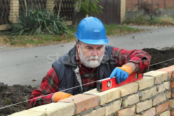 Worker examining brick wall using level tool Stock photo © simazoran