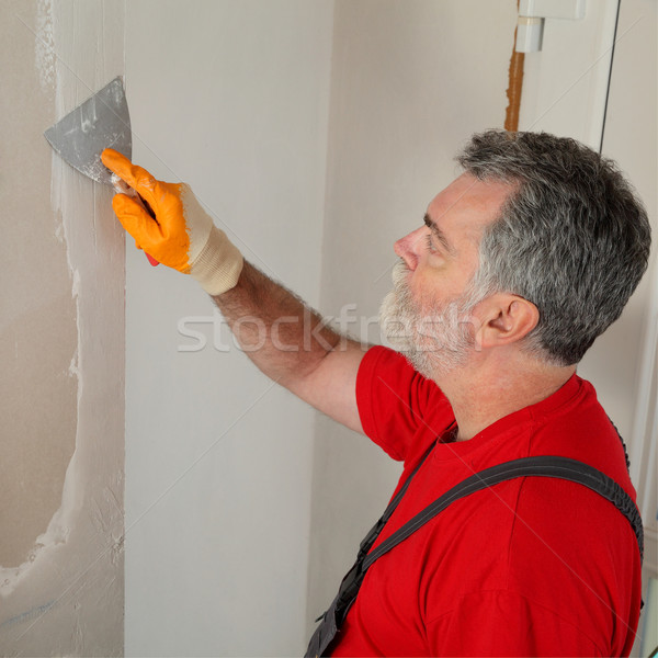 Construction site, worker installing gypsum board Stock photo © simazoran