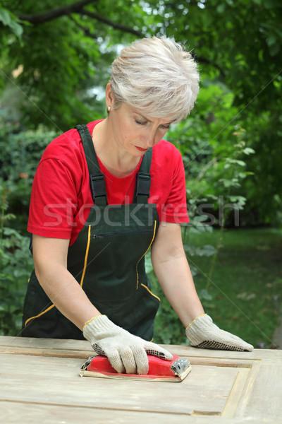 Female worker restoring old wooden door Stock photo © simazoran