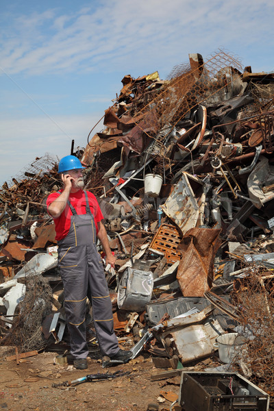 Recycling industry, worker using phone and heap of old metal Stock photo © simazoran