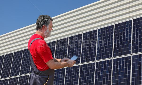 Solar energy, worker and panels Stock photo © simazoran