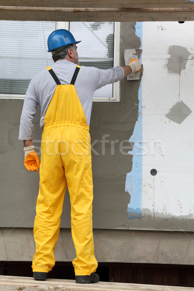 Wall insulation, spreading mortar over mesh and styrofoam Stock photo © simazoran