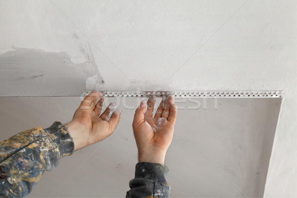 Worker install batten at ceiling and wall Stock photo © simazoran