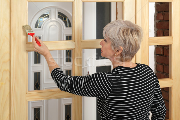 Adult female worker painting  wooden door Stock photo © simazoran