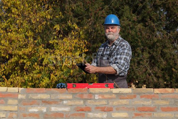 Worker examining brick wall, using tablet Stock photo © simazoran