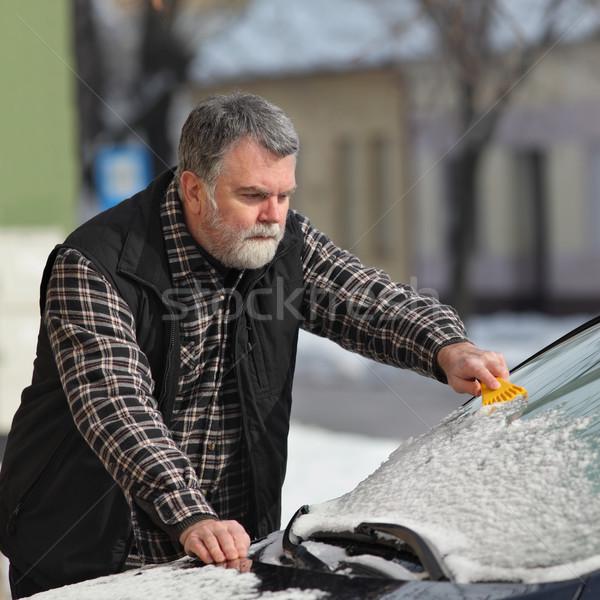 Winter scene, driver cleaning windshield of car Stock photo © simazoran