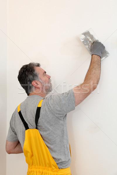 Worker repairing plaster at wall Stock photo © simazoran