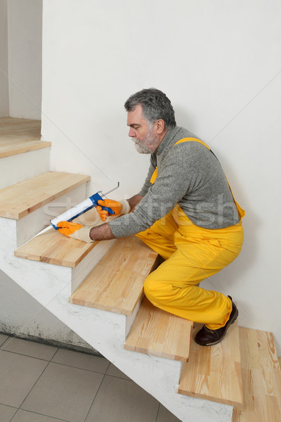 Home renovation, caulking wooden stairs with silicone Stock photo © simazoran