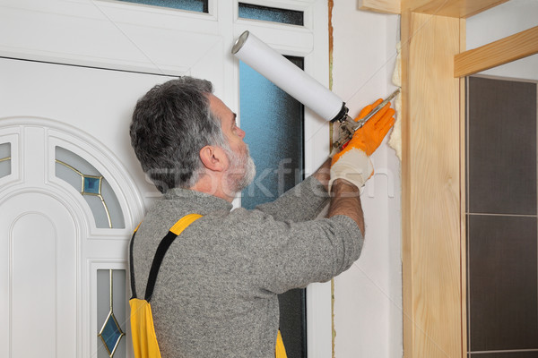 Worker installing wooden door, using polyurethane foam Stock photo © simazoran