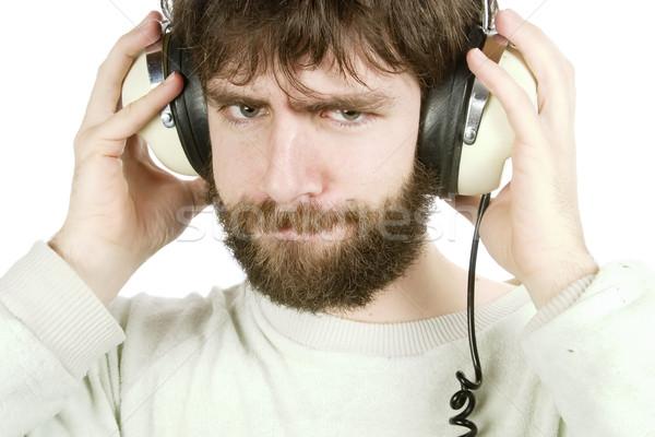 Sceptique musique jeune homme regarder écouter de la musique casque Photo stock © SimpleFoto