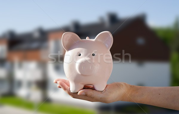 Woman's hand holding piggybank. New house in background Stock photo © simpson33