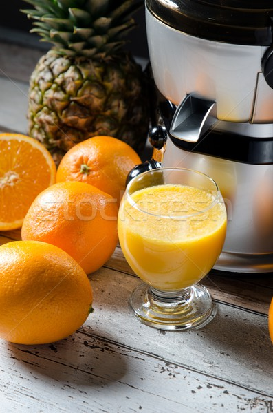 Juicer and orange juice in glass on wooden desk Stock photo © simpson33