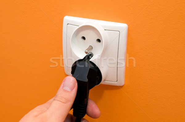 Hand put plug into electrical socket in wall Stock photo © simpson33