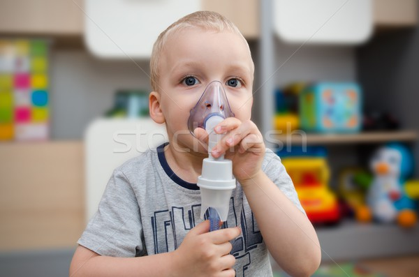 Child making inhalation with mask on his face.  Stock photo © simpson33