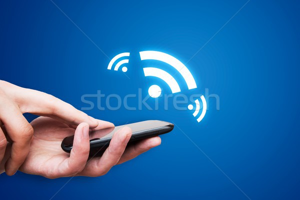 Stock photo: Hand holding smartphone with NFC technology - near field communi