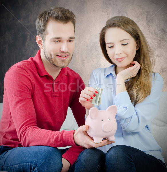 Young marriage puts savings into piggy bank Stock photo © simpson33