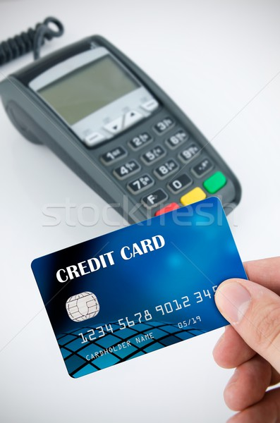 Hand holding credit card. Payment terminal in background Stock photo © simpson33