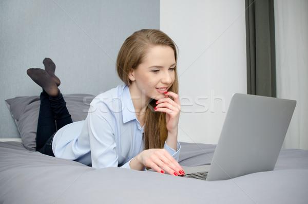 Mujer mentiras cama portátil estudiante sonriendo Foto stock © simpson33