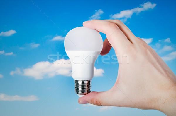 Hand holding LED bulb on sky background Stock photo © simpson33