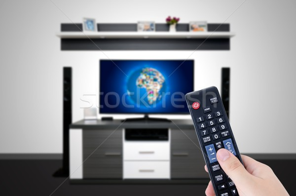 Stock photo: Watching television in modern TV room. Hand holding remote