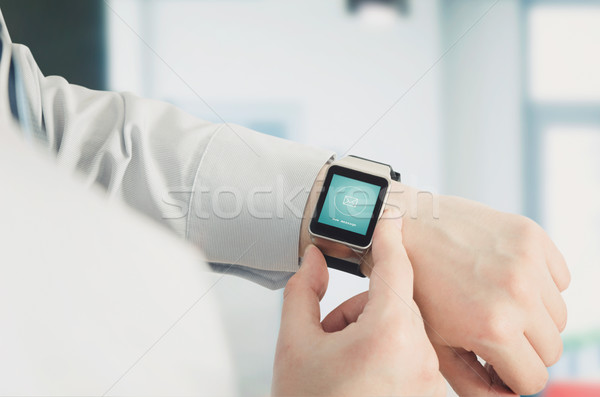 Man using smartwatch with e-mail notifier Stock photo © simpson33