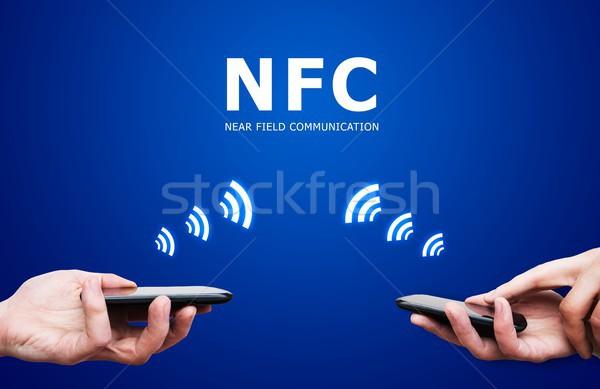 Stock photo: Hand holding smartphone with NFC technology - near field communi