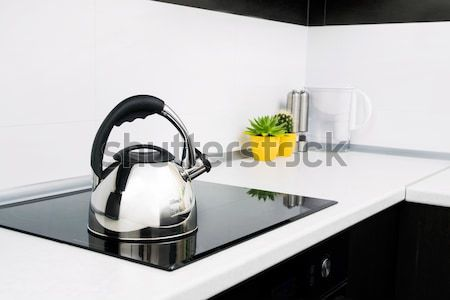 Steel kettle in modern kitchen with induction stove  Stock photo © simpson33