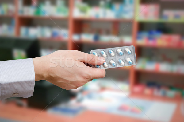 Stock photo: Pharmacist holding tablets in hands