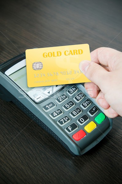 Man pays a gold card in payment terminal Stock photo © simpson33