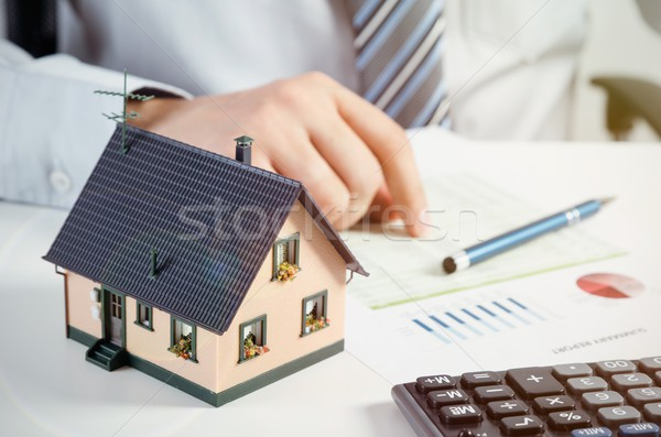Businessman calculate the cost of building and maintaining home Stock photo © simpson33