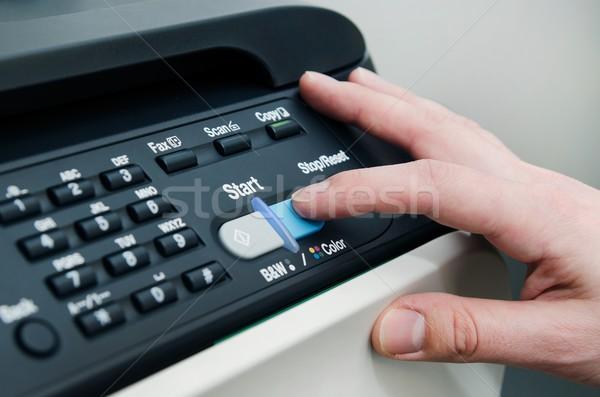 Finger on start button of laser printer Stock photo © simpson33
