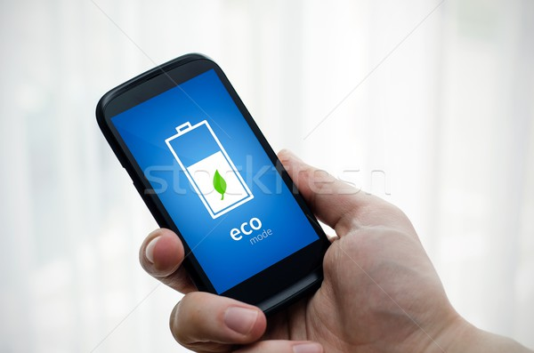 Man holding phone with eco battery mode on display Stock photo © simpson33