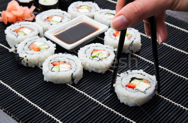 Woman's hand taking philadelphia sushi Stock photo © simpson33