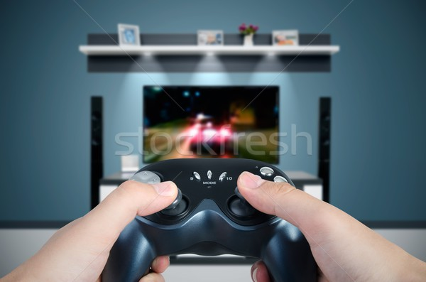 Hands hold the game controller. Man playing a car racing on TV  Stock photo © simpson33