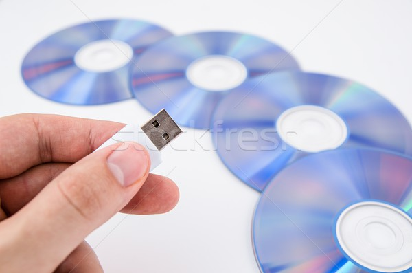 Hand holding USB drive. DVD discs in background Stock photo © simpson33