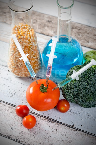 Syringe in tomato. Genetically modified food concept on wooden b Stock photo © simpson33