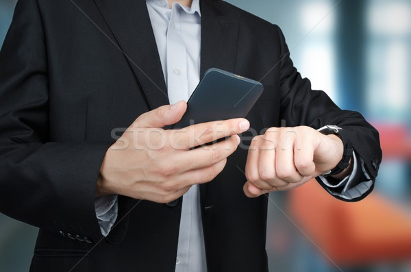 Businessman with smartphone and smartwatch in office Stock photo © simpson33