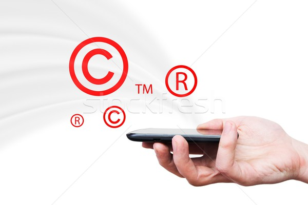 Copyright, trademark symbols flying from smartphone Stock photo © simpson33