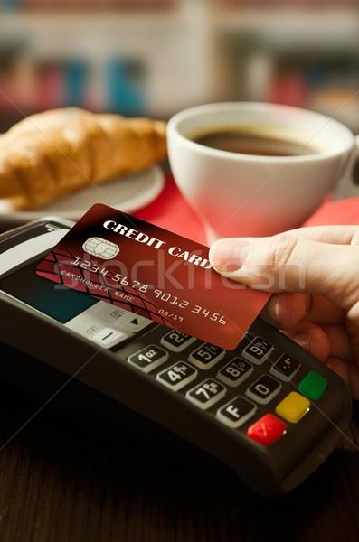 Stock photo: Man using payment terminal with NFC technology in cafeteria
