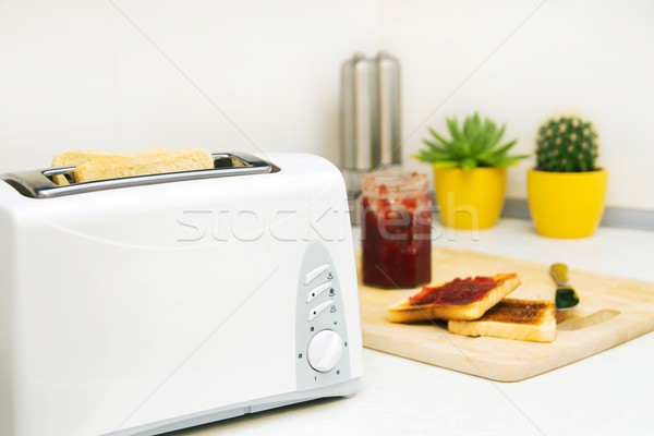 Breakfast prepare. Toaster and toast with jam in modern kitchen Stock photo © simpson33