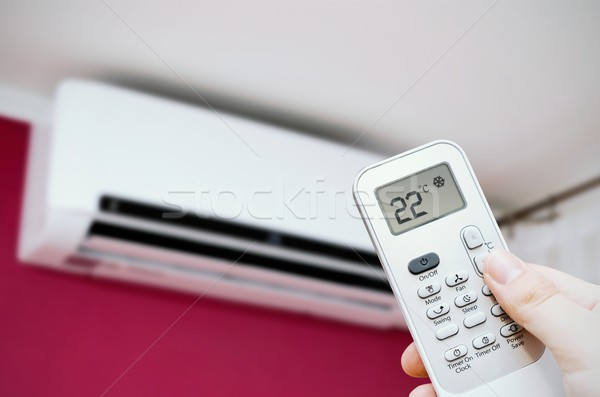 Air conditioner split. Hand holding remote control Stock photo © simpson33