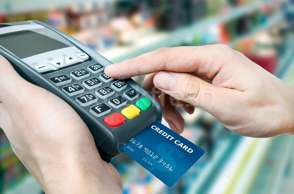 Hand with credit card swipe through terminal for sale in superma Stock photo © simpson33