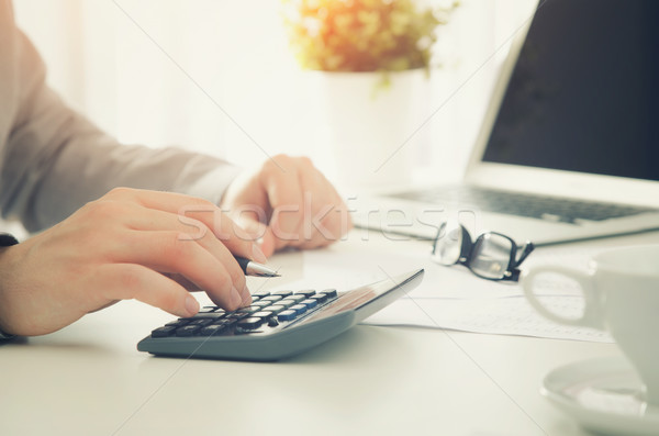Accountant calculates tax. Working in the office with calculator Stock photo © simpson33