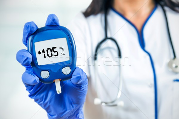 Closeup composition of woman doctor holding glucometer.  Stock photo © simpson33