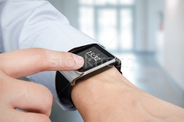 Businessman checking time on smart watch. Office in background Stock photo © simpson33
