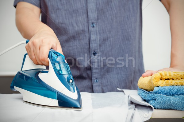 Man irons clothes on ironing board with blue iron Stock photo © simpson33
